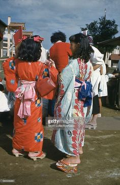Two Japanese women in colorful kimonos, viewed from behind, standing in a crowd, wearing traditional platform geta sandals, Japan, 1952.