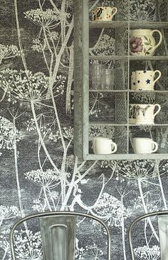 Emma Bridgewater pieces displayed against a background of 'Cow Parsley' wallpaper by Cole & Son.