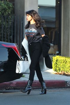 December 5, 2016 Selena wears a Coach graphic tee, black skinny jeans, leather booties, a slouchy two-tone cardigan and white Coach bag while out in L.A.