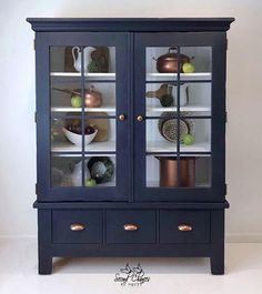 Misty Johnson here - painting this cabinet with Chalk Paint® by Annie Sloan in Napoleonic Blue and Black Wax, which gives it an unmistakeable navy blue. We love the copper touches of the handles and kitchen pots inside. Chalk Paint Cabinets, Painted China Cabinets, Painted Hutch, Chalk Paint Furniture, Painting Kitchen Cabinets, Annie Sloan Kitchen Cabinets, Annie Sloan Chalk Paint Projects, Annie Sloan Furniture, Bathroom Cabinets