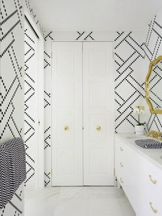 Amazing white, gold and black master bathroom with white and black textured patterned bathroom walls and bi-fold bathroom doors with antique brass door knobs.