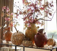 Heavy jugs, odd pumpkins, votives, leaves form a vignette.