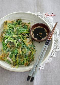 Spinach pancakes. Ingredients: spinach, onion, salt, flour, ice water, oil. Dipping sauce: soy sauce, lemon juice, sesame seeds. Recipe on Beyond Kimchee.