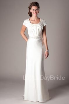 Arezzo | Elegant jewel scoop neckline is perfectly accented by a beaded trim of delicate rhinestones and sequins with a back neckline that features a piece of jewelry that accentuates the back of the dress. The sheath silhouette is finished with a beaded silk ribbon sash and matching fabric covered buttons along the entire length of the train.  Modest Wedding Dress | Modest Wedding Gown | LatterDayBride | LDS | SLC | UT | Salt Lake City | Utah | Worldwide Shipping |