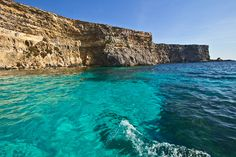 Sea cliffs of Comino rise vertically from exquisitely clear turquoise water surrounding the smallest of the Maltese Islands
