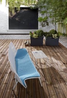 Ligne Roset's Grillage loveseat and table by François Azambourg and Giardinetto plant holders, featured in an outdoor setting.