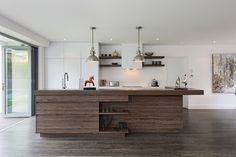Whit cabinetry with timber island bench.   Clever use of timber shelves to tie the kitchen together
