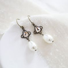 These lovely earrings are the simplified version to compliment the Anna collection. Beautiful antiquebrass filigree connectors are accented with Swarovski golden shadow rhinestones and finished with Swarovski ivory pearl drops. Earrings measure about 1-1/2 inch.This is an original design by © Treasures by AgnesPLEASE