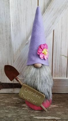 This garden gnome is wearing cotton candy pink and a lavender hat with big pink flower. Hes holding his garden shovel ready to plant his garden! He stands 9 inches high.