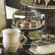 """Cream Covered Dessert Pedestal - Burnished Bronze by The GG Collection. $96.00. Handcrafted of ceramic and aluminum. Contains: Stand, plate & cover. (Overall) 8.5""""w x 8.5""""d x 8.75""""h (Plate) 7.25"""" dia (Dome) 6.25"""" dia x 4.5""""h. Beautiful, Italian-inspired, ceramic serving pieces by the GG Collection. Showcase your confections in style with this gorgeous old world style Dessert pedestal. These petite handcrafted pedestals from the GG Collection beautifully display and serve ch..."""