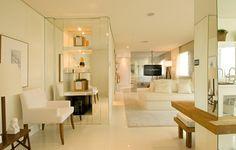 O jogo de espelhos e os revestimentos de piso e parede brancos deram unidade ao imóvel planejado pela arquiteta Débora Aguiar, que também optou por mobiliário no mesmo tom, em contraponto à madeira