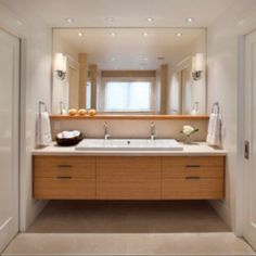 Love the double sinks that abutt and the long shelf below the mirror. Also love sliding doors entry and light wood (with concrete floor)