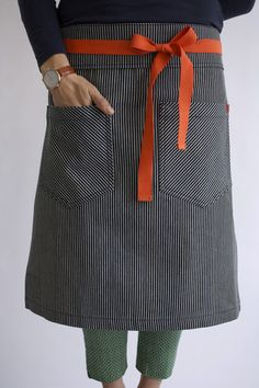 Knee-length pinstriped apron with cool pockets. Sorta menswear inspired.