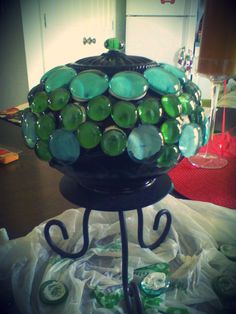 Garden Globe   Made out of :   A old light ficture,   A candle stand,   Some dollar tree stones.