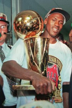 Chicago Bulls' Michael Jordan holds the NBA Championship trophy after the Bulls beat the Seattle SuperSonics 87-75 Sunday, June 16, 1996, in Chicago to win their fourth NBA Championship. (AP Photo/Beth A. Keiser)