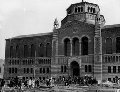 (1929) - Exterior view of Powell Library at the UCLA Westwood campus. Students are seen walking to and from the library, amid the construction activity.
