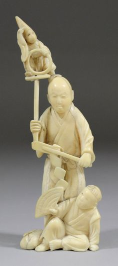 A Japanese carved ivory group of two figures and a monk : Lot 630