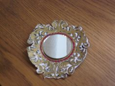 Mirror mirror on the wall....  This is a tiny mirror that I got from the local Dollar Store in a bag of about 10 or so. The frame was from a scrapbooking page filled with assorted frames, cut it out and embellished it with paint after gluing it to cardstock. It's going to go into the Evil Queen's room :)