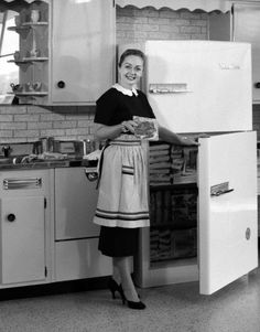 1950s housewife in kitchen taking food out of refrigerator.