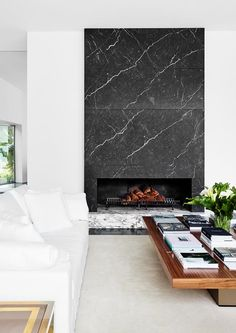 A monochrome living room with a marble fireplace. fireplace, A contemporary home with Californian appeal Cosy Fireplace, Modern Fireplace, Fireplace Wall, Living Room With Fireplace, Fireplace Surrounds, My Living Room, Contemporary Fireplace Designs, Marble Fireplaces, Vintage Chandelier