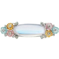 Raymond C. Yard Moonstone Brooch with Floral Surround    Moonstone brooch in platinum, composed of a large central moonstone surrounded by blue topaz, pink tourmaline and citrine carved in the shape of flowers and accented by round brilliant cut diamonds. Moonstone weighing 23.96 carats and 18 diamonds weighing 0.97 total carats. Signed Yard.