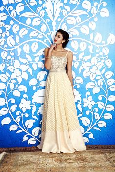 A cream jacquard gown with intricate gota patti embroidery is placed perfectly along the yoke.