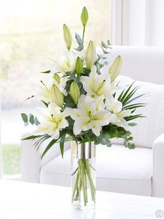 Featuring white oriental lilies with palm leaves, bear grass, eucalyptus and salal, presented in a tall ceramic vase with gold voile ribbon by Flowers.ie. Order Flowers Ireland