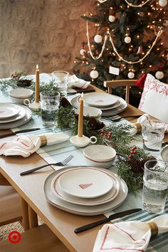 """Nothing says """"holiday"""" like a dining table set with dinnerware and linens in classic red and green. Style the table with napkins, candles and faux garland, and then get comfy with some holiday themed toss pillows. #HearthAndHand Christmas Dining Table, Christmas Table Settings, Christmas Tablescapes, Christmas Table Decorations, Holiday Tables, Holiday Decor, Cozy Christmas, Christmas Holidays, Deco Table Noel"""