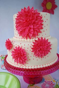 """Cake is 9"""" and 6"""" with hot pink gumpaste dahlias in different sizes; it's lemon cake with strawberry buttercream covered in fondant."""