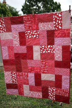 easy lap quilt by tcockburn2002, via Flickr  I cut 10 x 5 rectangles from various red fabrics, created blocks using two different red panels, and then did a fence row-esque pattern, alternating vertical and horizontal placement. Simple straightline quilting and used strips of reds for my binding. Used a bedsheet for the backing in a nice grey.