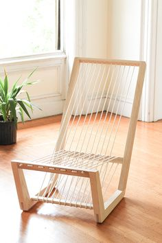 A lounge chair made from a single board of ash, an uncut length of cord, and cork details.