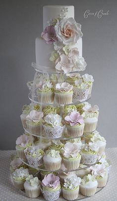 Beautiful cupcake and wedding cake tiered display with fondant flowers in a palette of pink, yellow and white