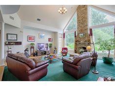 Lareira de pedra do chão ao teto aninhada entre duas janelas expansivas para esta sala de família