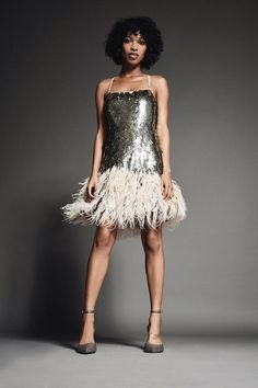 8b964a3e A stylish woman dressed formally in a silver sequin dress with spaghetti  straps and white feathers