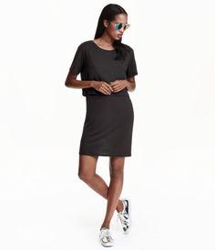 En kort klänning i mjuk trikå med lyster. Klänningen har ett extra lager upptill och kort ärm.