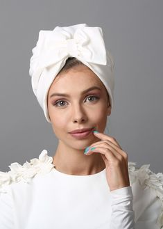 Bow style turban in elegant white. The Turban is stretchy, light, and comfortable. This versatile turban can be worn as a full or partial head covering. Tuck all of your hair in, or wear as a hat, with hair loose.