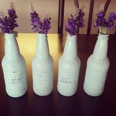Glass soda bottles painted on the outside with some pretty false flowers to make up a nice country chic center piece for the table