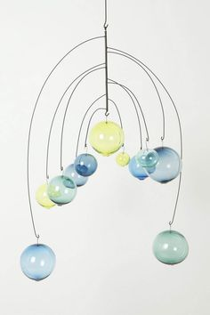 you could totally do this with hangers, clear glass Christmas bulbs and whatever colors of paint you want by putting different layers of paint in the bulb one layer at a time...then it would create a way cool ty dye effect...