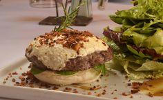 Hambúrguer de Cordeiro com queijo de cabra brûlé, farofa de bacon, pasta de hortelã picante sobre brioche com folhas ao molho da chefa, servido mal passado