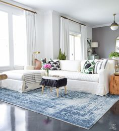 vinatage inspired blue rug white slip covered couch fiddle leaf fig plants in houston tx tall plants houston black fur ottoman hicks pendant white linen drapes small space living summer decor -1