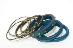 Juego de pulseras de aro azules: 3 de madera con tachuelas y 4 de metal dorado envejecido labradas    Medidas diámetro 7 cm  Ref.: AG7450A  http://www.meigallo.com/articulo/706/set-de-pulseras-rigidas