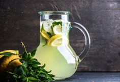 Homemade lemonade with mint, lemon slices and ice over dark background, copy space
