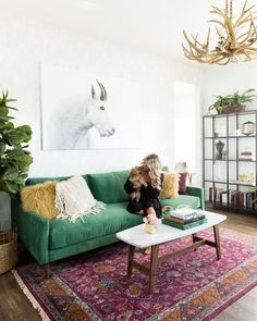 green sofa + rug + textiles + white wall + large art