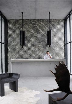 Hotel Habita in Monterrey, Mexico. Behind the minimalist, concrete front desk visitors can admire a wall mosaic made of hand-made mirrored tiles brought from India. Every single space in the hotel is sleek, dramatic and filled with timeless classics like Swan Chairs by Arne Jacobsen and furniture from avant-garde designer Rick Owens. The hyper-modern interiors were created by Parisian design extraordinaire Joseph Dirand