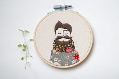 Embroidery Hoop Art -  It is a 4 inch stitched illustration of a male with flowers in his beard. He is wearing a floral pattered shirt. #elenacaron #hipster #presentfor guys #beards #beard # embroideryhoopart #embroidery #custom #art #textile #textileart #handstitch #hipsterart #present #homedecor