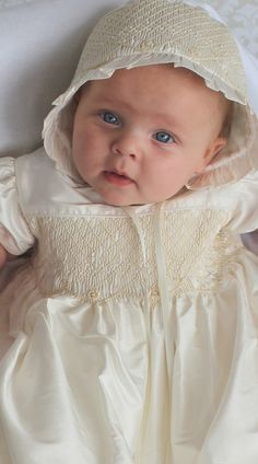 Abigail is a beautiful 100% Dupioni Silk Christening gown with hand-smocked bodice in ecru, seed pearls accents along the bottom embroidery on the bodice and bonnet, and finished with tucks along the