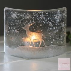 PLEASE NOTE DUE TO HIGH DEMAND THERE IS A TWO WEEK WAITING LIST FOR THIS PRODUCT.  A beautiful curved peice of clear glass in my new Christmas Stag design which looks magical when lit with a tea light candle or simply placed by a window to catch the sun light. The glass is embossed with a stag and snowflakes and is sprinkled with white glass snow.  Your tea light curve will come beautifully packaged in white tissue and the back of the glass can be engraved with dates for ...