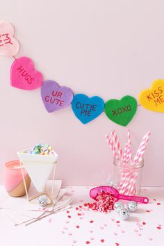 Decorate for Valentine's Day with this simple, no-sew felt DIY conversation heart banner with a variety of colorful hearts painted with fun sayings inspired by conversation heart candies!