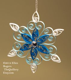 This is a one of a kind, handmade quilled Christmas Ornament in a snowflake design. It is made with pearlized blue, light blue and white paper with a