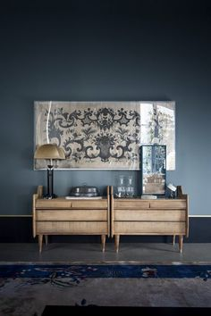 Blue-grey walls; low, low part of wall painted dark separated by thin white line; bleached out wood; worn-out/vintage'y framed textile; little hit of brushed brass